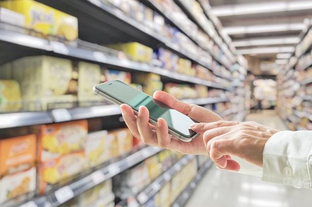 Mão segurando celular em frente a gôndola de supermercado