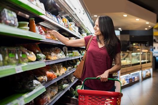 Gôndola de supermercado cheia de produtos e consumidora escolhendo