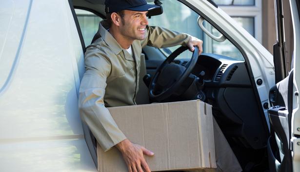 Entregador com caixa de papelão saindo de uma van