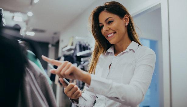 Lojista conferindo roupas no estoque